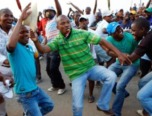 Image: Striking miners dance and cheer after they were informed of a 22 percent wage increase offer outside Lonmin's Marikana mine